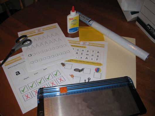 1- Gather your supplies! You will need your file folder printables, scissors, a trimmer (if you have one), glue, one file folder, one CD envelope and laminating material (I use contact paper).